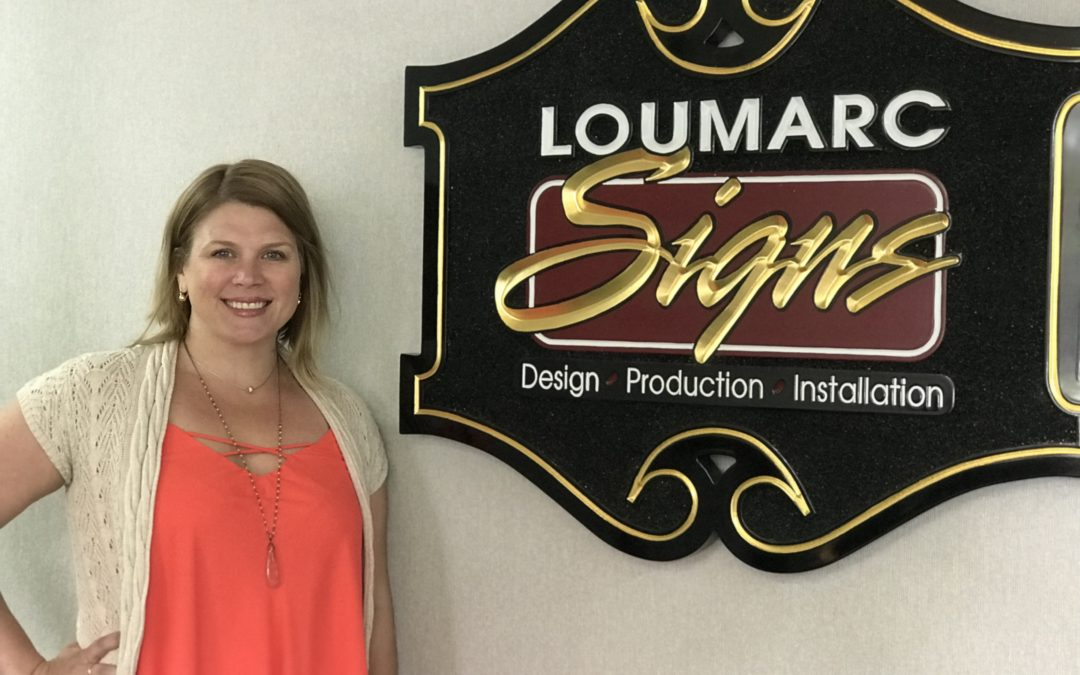 Teri Olsen with Loumarc Signs sign